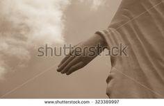 Buddha hand statue sculpture closeup focused on fingers sepia tone
