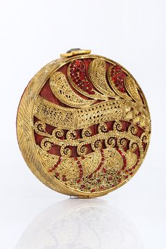 Featuring a timeless piece, this circular clutch is crafted in raw silk with a generous dose of stunning golden embellishments. It is rendered with gorgeous metal work in flattering patterns, scattered along the piece. This luxurious designer accessory offers a metal lock for closure and is enhanced with a comfortable design, to match you look.
