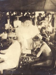 """Miss Zamora, the native Filipino teacher instructing an Igorrote pupil in reading."" (1904 World's Fair, Philippine Reservation). Missouri History Museum"