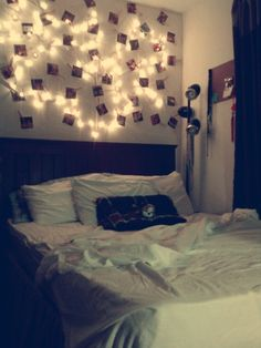 romantic bedroom. used string lights, clothes pins, and pictures.. its an extension of my headboard.