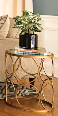 The answer to finding a unique piece is the Tabitha Bronze Accent Table. The metal circle design includes a mirror top to place everyday items. Shop online now. #LivingSpaces
