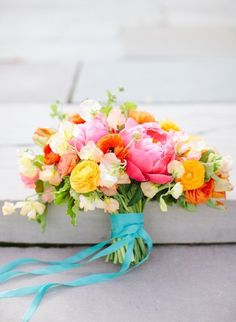 Gorgeous wedding bouquet in sherbety pastels with turquoise with pink peonies, yellow ranunculus and sweet peas
