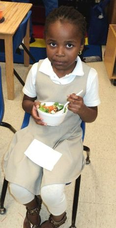 Young girl enjoying a salad at Jackson-Madison County Schools in Tennessee.