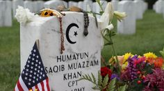A growing collection of flowers and American flags surrounds the headstone of Capt. Humayun Khan in Arlington National Cemetery near Washington, D.C. Americans…