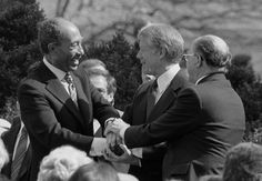 President Jimmy Carter shakes hands with Egyptian President Anwar Sadat and Israeli Prime Minister Menachem Begin at the signing of the Egyptian-Israeli Peace Treaty on the grounds of the White House. Jimmy Carter, Camp David Accords, Menachem Begin, President Of Egypt, Arab States, Muslim Brotherhood, Israel News, Nobel Peace Prize, Dangerous Woman