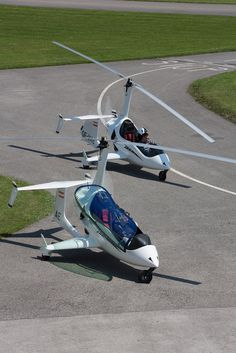 Arrowcopter USA AC20, one with open cockpit & one enclosed, sitting on runway.