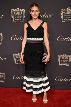 Olivia Palermo in a lbd with a midriff-revealing netted panel and a black-and-white flouncy hem, a graphic box clutch and metal-cuffed sandals.
