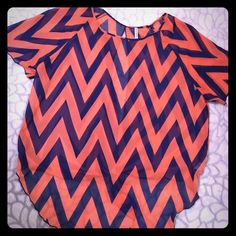 Chevron short sleeve pullover blouse Pinkish/peach with navy blue chevron patterns all over blouse. Light weight material. 100% polyester. On back has two gold sphere buttons one on top & the other on middle. Can be tied or let loose on back of blouse. Beautiful colors for upcoming Spring. Flash Tops Blouses