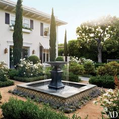 Devised by the Los Angeles firm Modern Floristry, the Italianate garden in the entrance courtyard includes a pair of lead fountains (one is shown) from Authentic Provence.