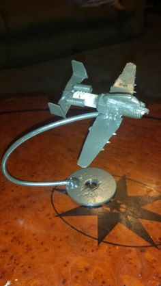 Plane made from a spark plug and other scrap metal. Check us out on Facebook. Search American Metal Art.