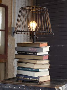 Make a stacked-book table lamp using hardcover books, a lamp kit, lamp shade, drill, and screwdriver. (The post links to a how-to/tutorial.) #DIY