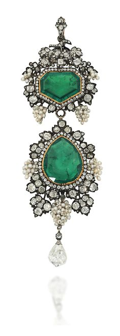 A LATE 19TH / EARLY 20TH CENTURY EMERALD AND DIAMOND BROOCH / PENDANT. The surmount with fancy-cut emerald and single-cut diamond cluster centre, to a fruiting vine surround, composed of bunches of seed pearl grapes among old-cut diamond-set vine leaves, suspending a pear shaped emerald drop with similarly-set seed pearl and diamond border, to a further briolette-cut diamond terminal, mounted in silver and gold, 10.7cm long, later fitted retailers case