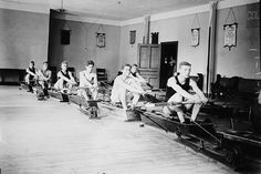 The Columbia rowing team exercising indoors with rowing machines, 1910.