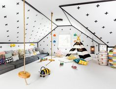 Black and white attic playroom features a ceiling and walls clad in Urban Walls Plus Signs Decals lined with charcoal gray tufted cushions lined with pillows illuminated by yellow sconces facing a pair of rope and wood swings suspended from the ceiling.
