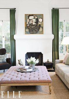 White and green living space with abstract art above fireplace