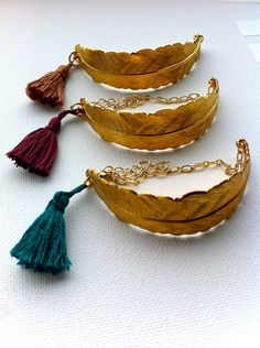 Bracelet with large brass feather, chain and colourful tassel. €25,00, via Etsy.