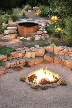 Rustic setting for a classic wooden hot tub, nestled into rocks & boulders. The theme continues downhill for the fire pit, and a bench built of rocks...