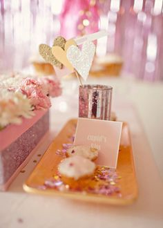 Cupids kiss cupcakes and pink flower centerpieces with sparkly bands