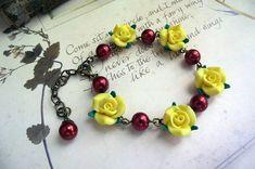 Adorável pulseira de rosas amarelas de biscuit, entremeadas por pérolas vermelhas.  Comprimento:17 cm, mais extensor de 4,5 cm (total: 21,5 cm) R$ 22,00