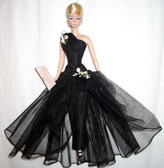 Evening dress in black glitter illusion over silk. One shoulder bustline treament, dropped waist overskirt. Vintage flower accents. Pink silk