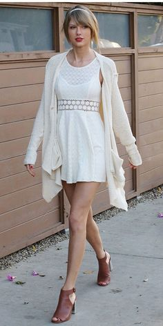 Taylor Swift wears a white crochet dress, cardigan, and brown heeled sandals