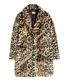 Leopard print. Short faux fur coat with lapels, buttons at front, and welt pockets. Vent at back. Lined.