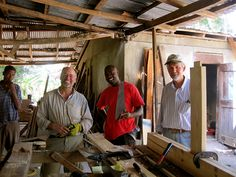 Service-learning trip volunteers George Wootton and Rob Ehler assist local carpenters on a door. Photo taken on   UUSC-UUA JustWorks Haiti Volunteer Program trip, December 2011 trip.  Location: Colladere, Haiti  Photographer: Nicole McConvery