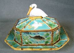 circa 1870 George Jones Majolica sardine dish, cover & stand. Cover is decorated with flying pelicans, white flowers with green leaves, bamboos, a pelican forming finial on top. Dish has panels, separated by bamboo, depicting fish, pond lily leaves and flowers on a rippled water effect ground. Mottled green & brown underside. Pink interior. The stand has a mottled green & brown center surrounded by bamboo. Mottled green & brown underside. Impressed GJ monogram & painted ''5449'' to…