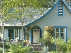 Make a nod to your home's environment with a color palette that matches its surroundings but still packs curb appeal. This traditional home's soft pine green base pops with an accent of sky blue and an understated creamy white door. Paint colors: Nature's Gift, Restless Sea and Twinkling Lights by Behr