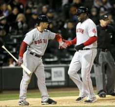 Boston Red Sox's Daniel Nava, left, greets David Ortiz at home after Ortiz scored on A.J. Pierzynski's sacrifice fly during the eighth inning against the White Sox on 4-16-14 in Chicago. The Red Sox won in 14 innings, 6-4.