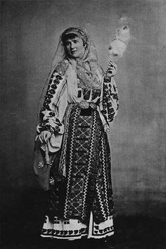 A royal portrait employing strong mythic overtones: Queen Elisabeth of Romania, born a German princess, adopts the national costume of Romania, with distaff and spindle. 1882