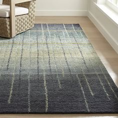 Handtufted with a sumptuous pile, this gorgeous rug features swaths of graduated greys accented with slim stripes and touches of golden and blue. The coloration gently flows from pale grey at the center to deep and dark grey at two edges. The pure wool ru