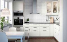 Cucina bianca con elettrodomestici in acciaio inossidabile, sedie ...