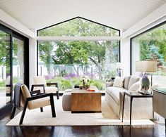 Interior designer Joan Hebert chose neutral colors for upholstery to marry with ebony wood tones and let outdoor views remain the primary attraction in this sunroom. - Photo: Werner Straube / Design: Mick de Giulio