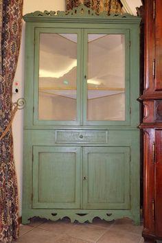 Vetrina ad angolo laccata verde, con intagli nella parte inferiore e superiore, interni foderati in stoffa, con quattro ante e un cassetto. Periodo primi '800, restaurata.