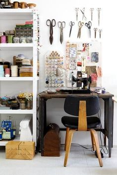 Sewing workspace with scissors on wall.