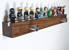 """Hang your hangables from the two hangers.Display your favorite 13 Lego� minifigs in serious style.USA sustainably harvested Walnut.Lego� blocks permanently bonded into wood.Individually hand-made in Oregon, USA.Finished with food safe artisanal oils.Shelf hanging slots for simple, invisible wall mounting.16.4"""" x 1.75"""" x 1.75"""" 1.25"""" hangers41.6cm x 4.45cm x 4.45cm 3cm hangersMinifigs not included.Walnut grain varies in pattern and darkn..."""