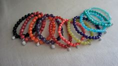 Rainbow of semi-precious stone bracelets with pave crystal charms.