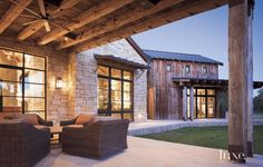 The house includes a series of interconnected barn-like structures. Far right, what appears to be an old barn actually houses the master suite. In the foreground, an outdoor porch is partially framed with log beams. Chairs from Restoration Hardware are clad in Perennials fabric from David Sutherland.