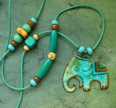 smaltovaný náhrdelník: velký slon Smaltovaný slon je v opálovo-modrých odstínech. Speciální francouzský opálový smalt dělá na světle měňavé barevné efekty.Šperkařský smalt na mědi je několikrát pálen v peci cca na 840 stupňu. Délší tyrkysovou kůži s korálky je možno individuálně nastavit posunutím korálku na konci . Velikost smaltu je cca 4:5cm