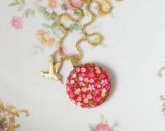Fabric covered button on a necklace with kolibri