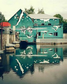 New York-based Ray Bartkus painted a scene of upside-down swans, swimmers, and rowers on a building in Marijampolė, Lithuania. When it reflects onto the river below, you see everything right-side up.