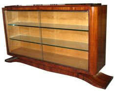 """This French art deco display case dates from the 1930s and is constructed from palissandre veneers with a sycamore interior.  The case rests on a raised plinth with lap feet.  Two 1/2"""" glass shelves sit behind sliding glass doors. The vitrine measures 58 ½"""" wide, 14 ½"""" deep and is 37"""" high."""