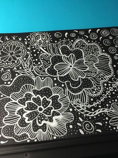 Zentangle with a white signo gel uniball pen on black paper.