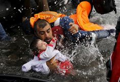 A Syrian refugee holds onto his children as he struggles to walk off a dinghy on the Greek island of Lesbos after crossing a part of the Aegean Sea from Turkey to Lesbos on September 24, 2015.
