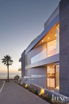 Hill Construction Company built the oceanfront house, which features a subtle curve along one façade. Glass railings provide a border between the house and a sidewalk that slopes down toward the beach. Patterson Engineering devised the steel and cast-in-place concrete frame to support a rooftop swimming pool.
