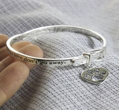 Lovingly crafted to resemble a pet collar, our bracelet serves as a beautiful reminder of your most cherished pet. A dangling paw print charm in the shape of a heart completes the accessory. Features a convenient adjustable strap to fit many wrists.