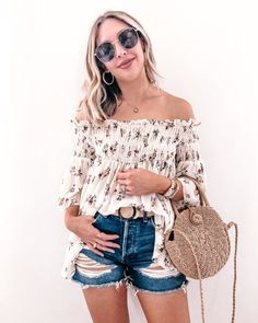 Bohochic casual summer outfit with a floral off the shoulder top, distressed cut offs (distressed denim shorts/distressed jean shorts), a woven belt, a straw handbag, metal framed glasses, thick gold hoops