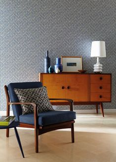 Midcentury indigo chair and teak cabinet against the wallpaper.