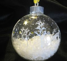 "Christmas ornament idea: clear glass ball, fill half with ""snow"", paint snowflakes & trees with a white or silver paint pen."